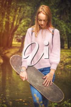 girl is holding a skate in the park