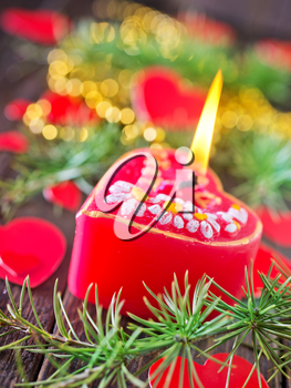 red candle and christmas decoration on the wooden table