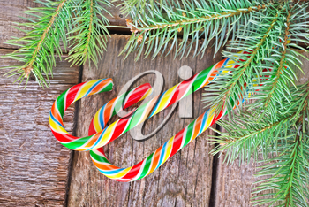 brunch of christmas tree and color candy on wooden background