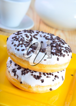 Delicious doughnuts on the yellow plate, donuts with chocolate