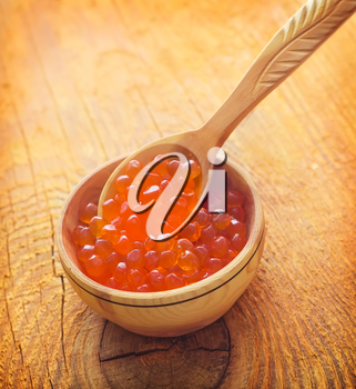 Red salmon caviar in the wooden bowl and spoon