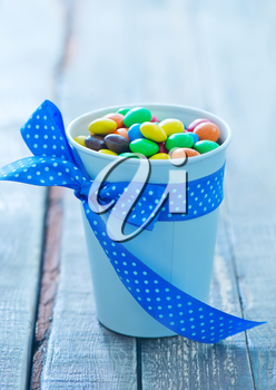 color candy in paper cup and on a table