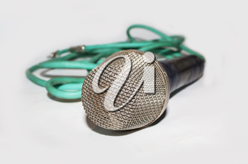 Microphone with green cable on light background