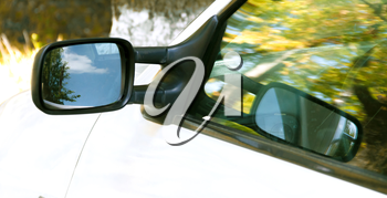Part of a moving white car with a reflection in the glass and mirror