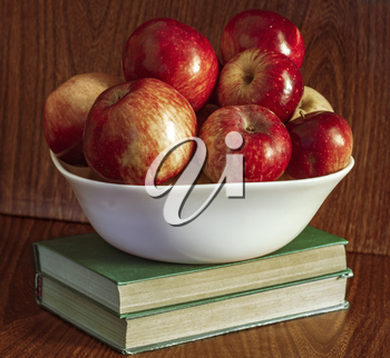 Vase with apples and books on a wooden background