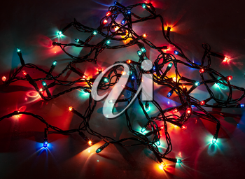 Background of colored lights garlands in the dark