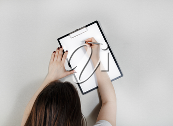 Clipboard with blank paper in female hands. Woman writes on blank white sheet of paper.