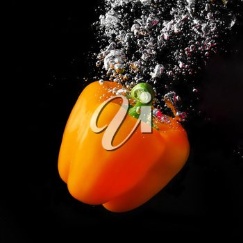 Fresh orange paprika falling into the water with a splash and air bubbles. Healthy food on black background. Wash vegetables.