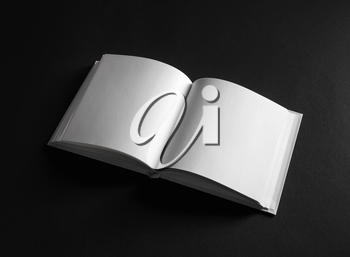Open blank square book on black paper background.