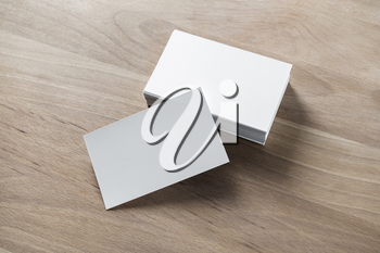 Blank white business cards on wood table background. Mockup for branding identity.