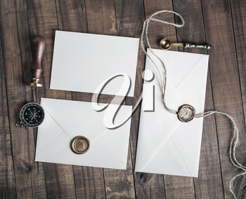 Vintage letter envelopes with wax seal, stamp, spoon, magnifier, compass and postcard on wood background. Flat lay.