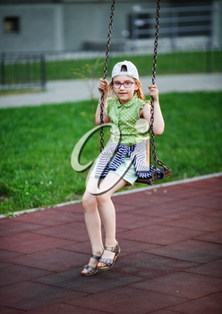 Serious girl on the swing. Child in the playground. Selective focus.