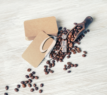 Blank retro business cards and roasted coffee beans on light wood table background. Business brand template.