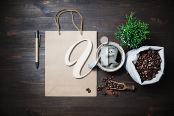 Blank kraft paper bag, coffee cup, plant, coffee beans in canvas bag and pen on wooden background. Top view. Flat lay.