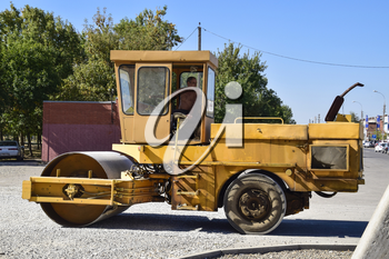 Slavyansk-na-Kubani, Russia - September 14, 2016: Rink compacted gravel. Working behind the wheel of the rink. Work on the creation of landscaped grounds.