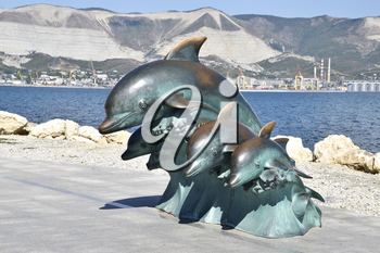 The bronze sculpture of three dolphins on the beach.