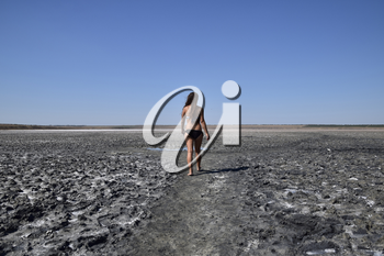 Woman walking along the dry bottom of a salt lake, rear view. Walk the dark-haired woman in a swimsuit on the bottom of a dry lake with salt and mud. The ancient dried-up lake.
