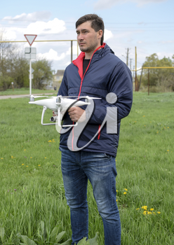 A man with a quadrocopter in his hands. A white drone is being prepared for the flight. Phantom