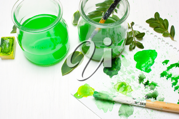 Green leaves draws the artist. Concept art. Workplace, designer table.Flat lay, overhead view