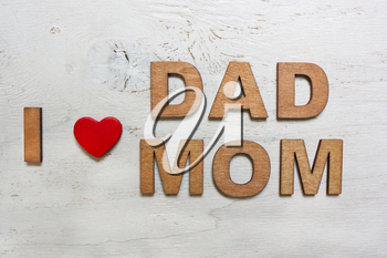 I love dad ,mom with wooden letters on an old white wooden background