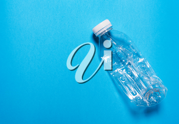 Plastic bottle on a blue background..The concept of sorting polyethylene, household waste.