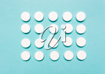 Round, white pills on a blue background. The concept of the treatment of the disease, healthcare, pharmaceuticals.