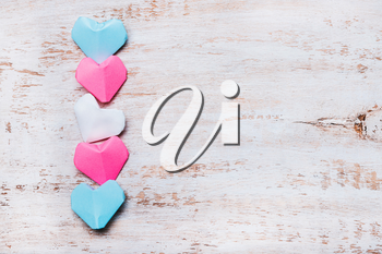 Origami paper hearts in transgender flag colors on wooden background