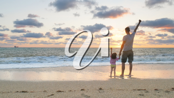 Father and daughter playing together on the sea beach at sunset. Emotional scene.