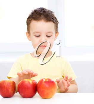 Portrait of a happy little boy with red apples