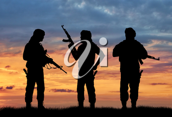 Terrorism and conflict. Armed terrorists on the sunset background