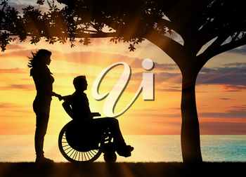 Concept of disability and disease. Silhouette of disabled person with a guardian on the sea sunset under the branches of a tree
