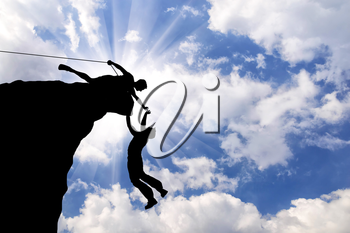 Concept of aid. Silhouette of two climbers help each other
