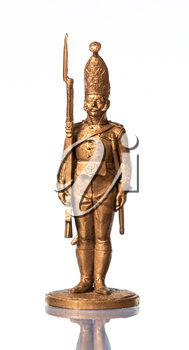Golden tin soldier on a white background with reflection.