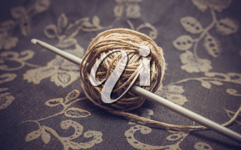 A ball of linen yarn and a crochet hook. Photo toned.