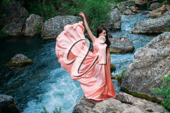 Young woman in gorgeous pink dress with waving flying fabric, fashion female posing in the park, near the river