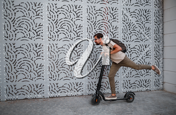 fun driving electric scooter through the city. A hipster man enjoys a walk through the city during the summer sunset. The idea and concept of ecology, style and fun moving around the city