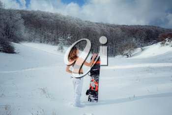 Female snowboarder hold snowboard and going to snowboarding. winter sport activity, forest snow outdoors lifestyle. Girl wearing a short top and ski white pants.