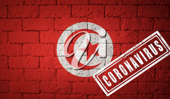 Flag of the Tunisia with original proportions. stamped of Coronavirus. brick wall texture. Corona virus concept. On the verge of a COVID-19 or 2019-nCoV Pandemic.