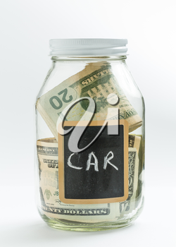Glass jar on white background with black chalk label or panel and used for saving of US dollar bills for car expenses