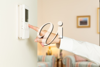 Caucasian female hand pressing button on a modern electronic thermostat timer on wall of a modern home with focus on the screen and fingers of the woman