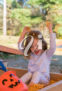 Young caucasian girl playing in the seeds from corn kernels and throwing them into the air at halloween pumpkin patch