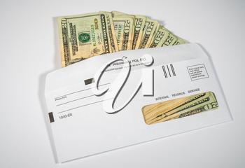 Stack of 20 dollar bills in IRS envelope to illustrate coronavirus stimulus payment or estimated tax payments on white background