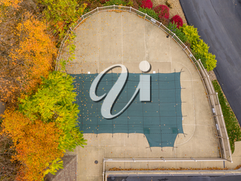 Aerial drone point of view of a green plastic cover on HOA swimming pool protecting it from leaves and for the winter storms