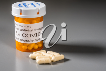 Prescription bottle and capsules illustrating trials of oral antiviral treatment for SARS-CoV-2 or Covid-19 virus
