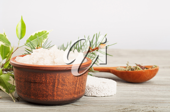 Aromatic bath salt in a clay cup and pumice stone on a wooden background.