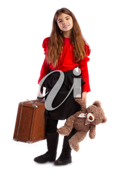 little girl packed her vintage retro suitcase and waits with her favorite teddy bear