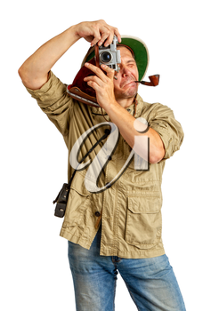 Adult Tourist in a tropical cork helmet and protective clothing with a pipe in his mouth photographs something on the old camera
