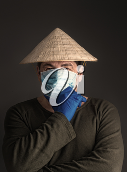 Chinese adult man in traditional Asian conical straw hat stands in virus-protected medical mask on a dark background