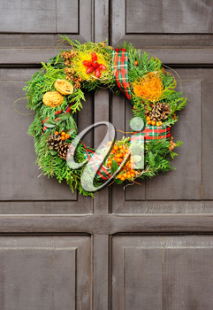 Nice Christmas wreath hanged on the wood door.
