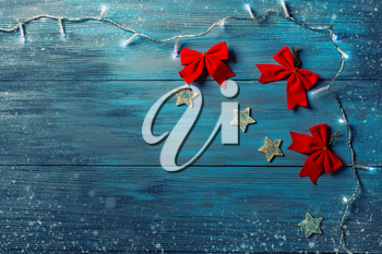 Blue wooden background and Christmas lights and decorations. Place for text.